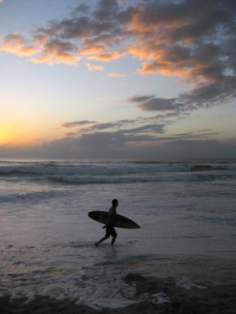 Colpo verticale di una persona che tiene una tavola da surf a piedi vicino a un mare ondulato durante il tramonto Foto Gratuite