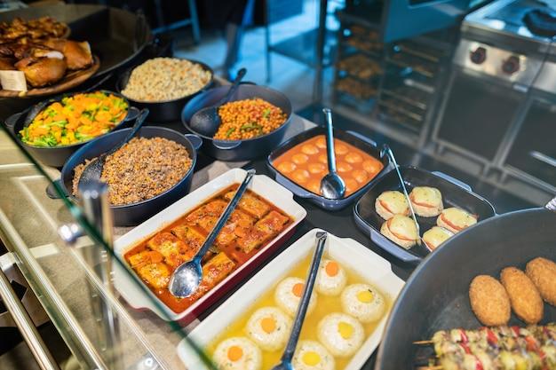 Colpo vicino di vetrine con cibo nella zona self-service del ristorante Foto Premium