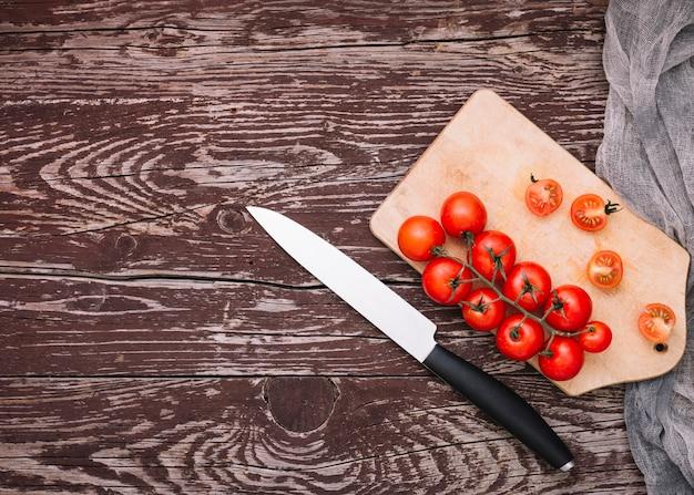 Coltello affilato e pomodorini sul tagliere sopra la superficie in legno Foto Gratuite