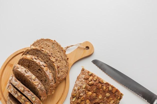 Coltello e fette di pane sul bordo di legno Foto Gratuite