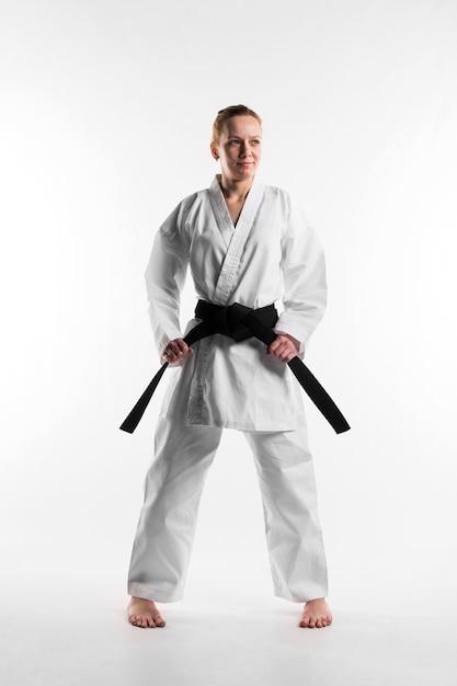 Combattente che tiene colpo pieno della cintura nera Foto Gratuite