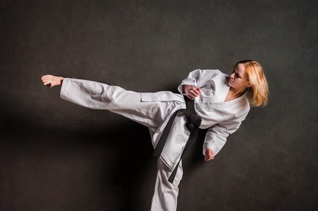 Combattente femminile di karatè che dà dei calci alla vista frontale Foto Gratuite