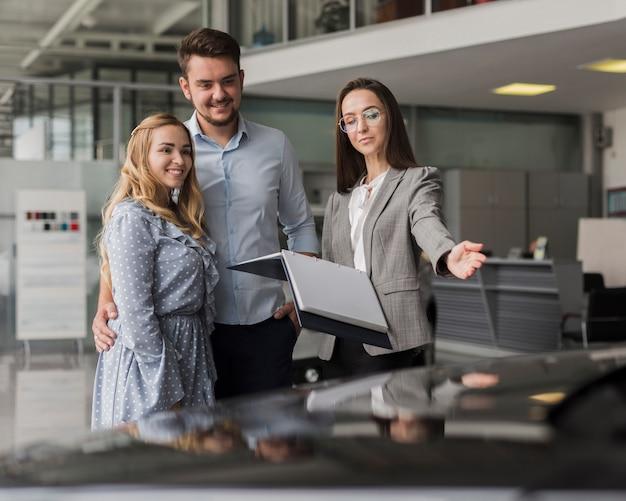 Commerciante di automobile che mostra un'automobile ad una coppia Foto Gratuite