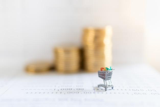 Commercio elettronico e concetto dei soldi. chiuda su della miniatura del carrello o del carrello sul libretto di banca con la pila di monete e copi lo spazio. Foto Premium