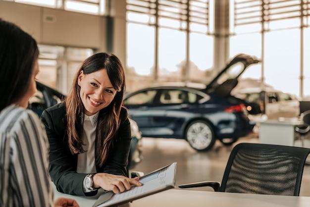 Commessa sorridente dell'automobile che discute un contratto con un cliente femminile. Foto Premium
