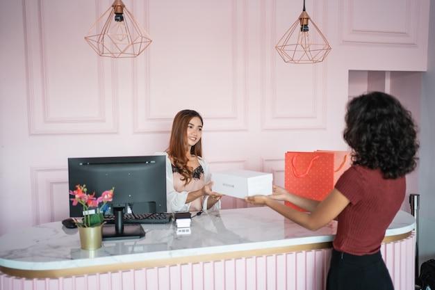 Commesso asiatico della donna con i contenitori di scarpe al deposito Foto Premium