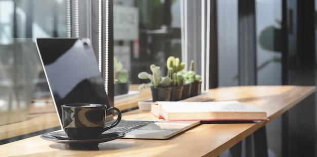 Comodo spazio di co-working con computer portatile e documento con decorazioni Foto Premium