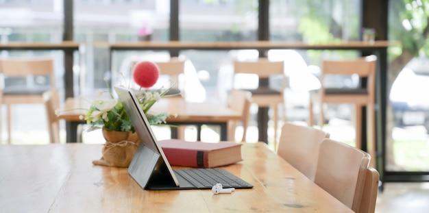 Comodo spazio di co-working con tablet con tastiera e decorazioni Foto Premium