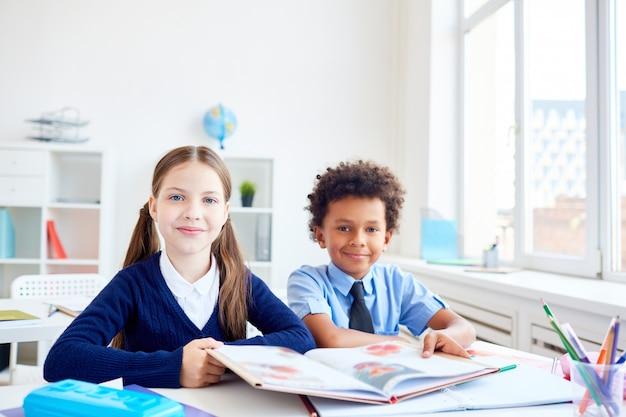 Compagni di classe alla lezione di lettura Foto Gratuite