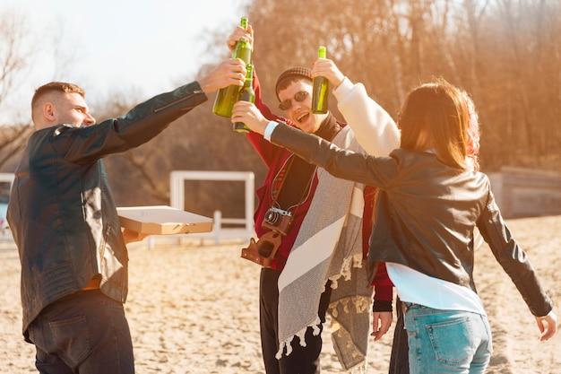 Compagnia di amici sorridenti divertendosi con la birra all'aria aperta Foto Gratuite