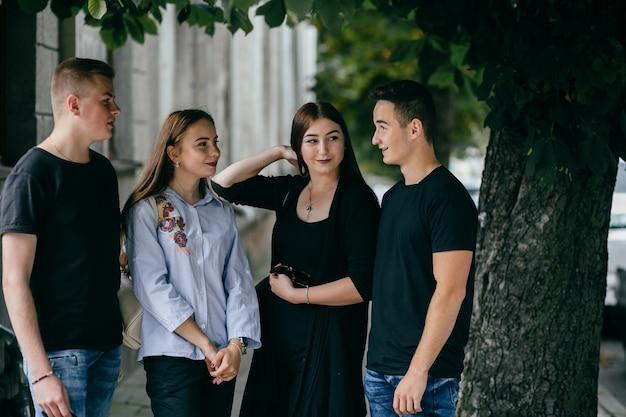 Compagnia di giovani amici con smartphone che camminano in città Foto Gratuite
