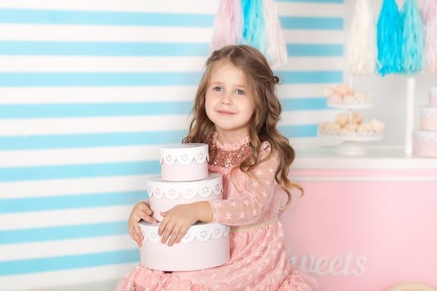 Compleanno! bella bambina che si siede con i regali. la barra del compleanno di candy. ritratto di un primo piano del viso del bambino. Foto Premium