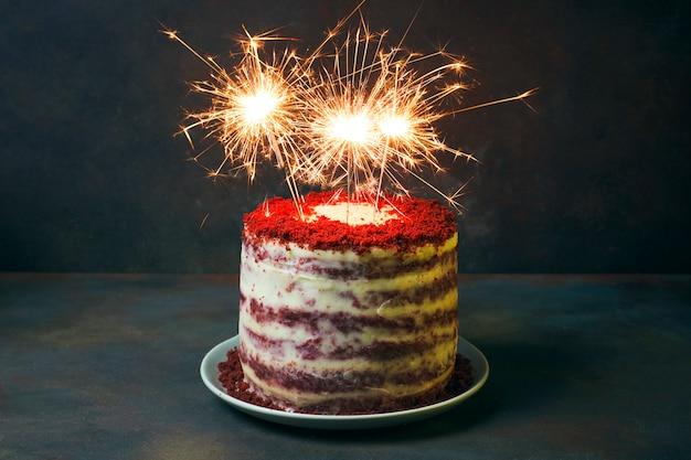 Compleanno di dessert festivo o torta di velluto dairato di san valentino con fuochi d'artificio Foto Gratuite