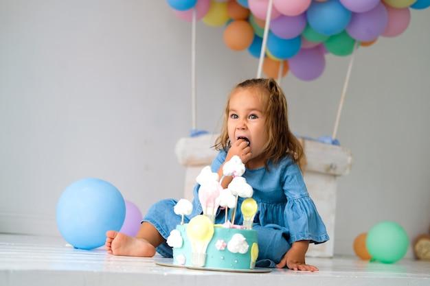 Compleanno ragazza felice di avere una torta di compleanno. sullo sfondo, un grande pallone giocattolo fatto di palline colorate. Foto Premium