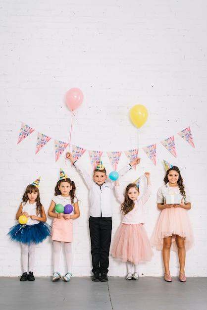 Compleanno ragazzo in piedi con le ragazze contro il muro bianco decorato con stamina Foto Gratuite