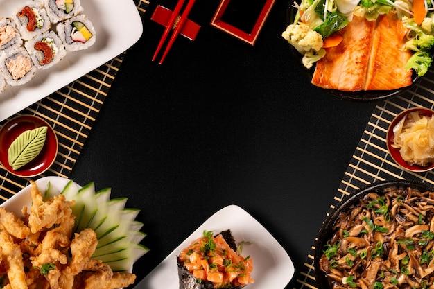 Composizione alimentare giapponese. vari tipi di sushi disposti sul bordo di pietra nera. insalata piccante di kimchi, bacchette e ciotola di salsa di soia. Foto Premium