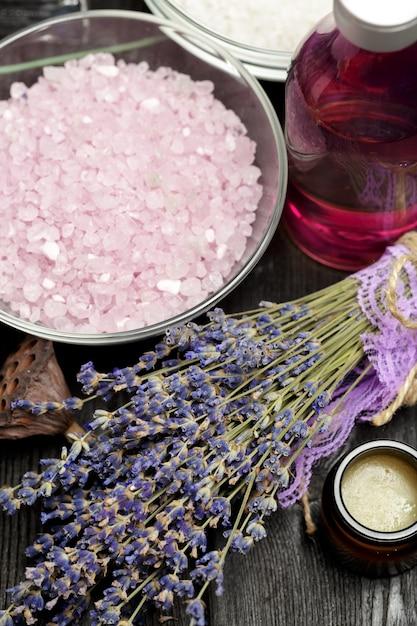 Composizione aromatica di lavanda, erbe, cosmetici e sale su un tavolo scuro Foto Premium