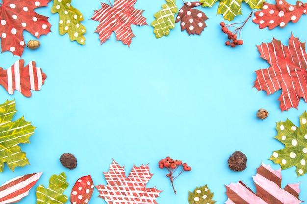 Composizione autunnale. cornice fatta di foglie secche creative acero, rovere dipinto con strisce, pois su sfondo blu. Foto Premium