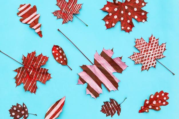 Composizione autunnale. cornice in acero foglie secche creative, rovere dipinto a righe, pois su sfondo chiaro. Foto Premium