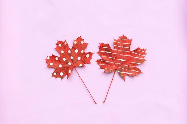 Composizione autunnale di foglie secche creative acero dipinto con strisce, pois su sfondo chiaro. Foto Premium