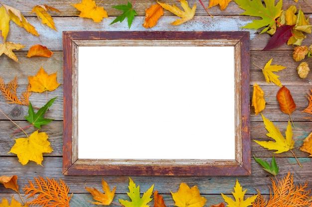 Composizione autunnale, foglie autunnali luminose e cornice su legno Foto Premium