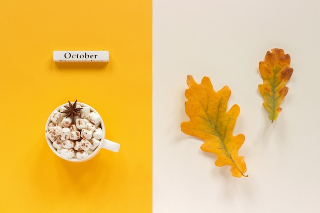 Composizione autunnale. mese di calendario in legno ottobre, tazza di cacao con marshmallow e foglie di autunno Foto Premium