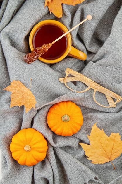 Composizione autunnale piatta con una tazza di tè e una calda sciarpa di lana Foto Premium