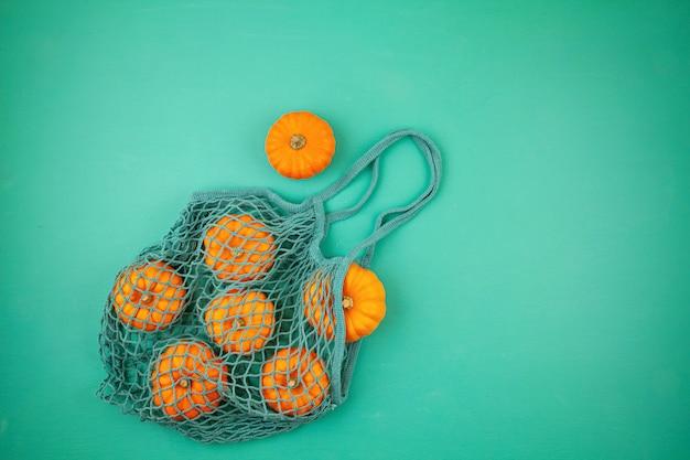 Composizione autunnale vista dall'alto con zucche nel sacchetto della spesa a rete su sfondo turchese Foto Premium