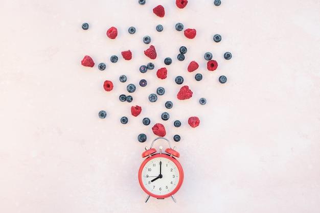 Composizione con bacche e sveglia rossa Foto Premium