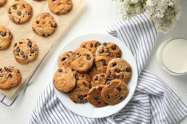 Composizione con i biscotti, i fiori e il latte di chip sulla tavola bianca Foto Premium