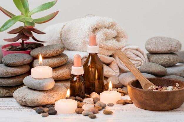 Composizione con pietre spa, candele accese e asciugamani Foto Gratuite