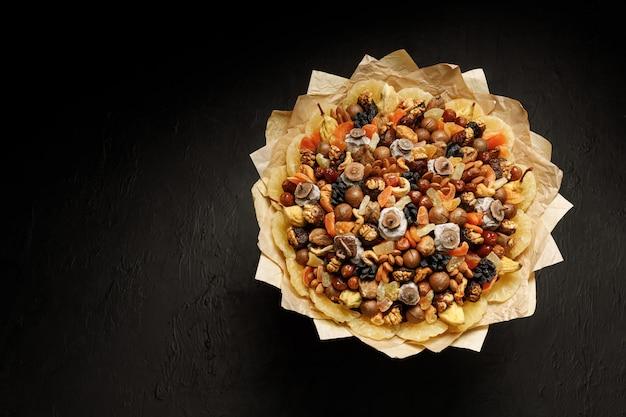 Composizione decorativa sotto forma di un bouquet di frutta secca e noci Foto Premium