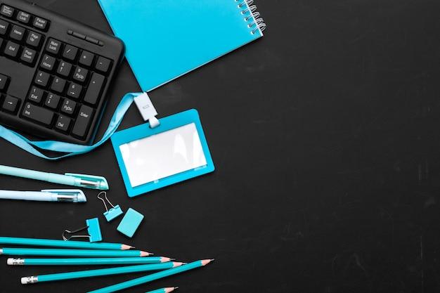 Composizione degli articoli per ufficio e dell'attrezzatura nei colori neri e blu fondo, vista superiore Foto Premium