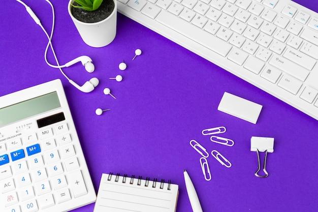 Composizione degli oggetti di stile di vita dell'ufficio su fondo porpora, articoli per ufficio della tastiera di computer sullo scrittorio in ufficio Foto Premium