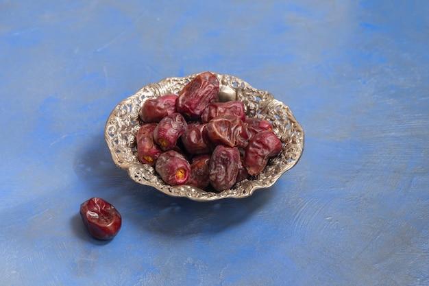 Composizione del digiuno del ramadan. datteri secchi in un piatto metallico Foto Premium