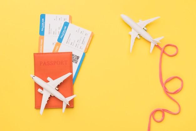 Composizione di aeroplani con passaporto e biglietti della compagnia aerea rosa Foto Gratuite
