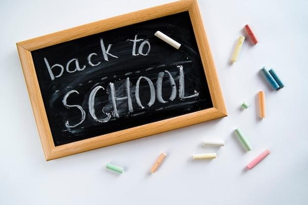 Composizione di back to school, nota a bordo e gessetti Foto Gratuite