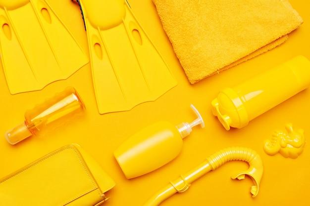 Composizione di costumi da bagno e accessori su un giallo Foto Premium