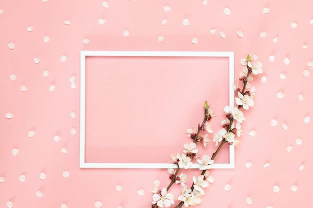 Composizione di fiori creativa. cornice in bianco, fiori rosa su sfondo corallo vivente, spazio di copia. Foto Premium