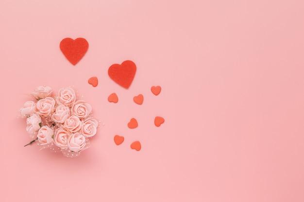 Composizione di fiori modello fatto di fiori rosa e cuori su sfondo rosa. Foto Premium