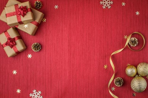 Composizione di natale con doni, palline d'oro, pigne, rami di abete e fiocchi di neve su un rosso Foto Premium