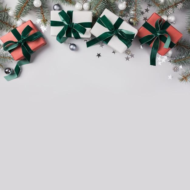 Composizione di natale con rami di abete, regali rossi sulla luce. carta natale. vacanze invernali. . Foto Premium