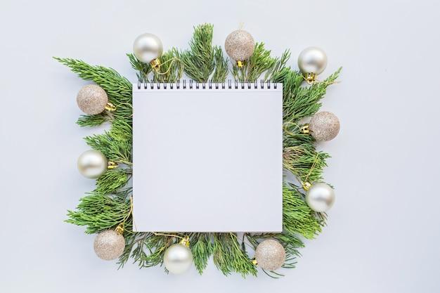Composizione di natale con spazio in bianco di carta, bagattelle, rami di abete su bianco. concetto di nuovo anno. Foto Premium