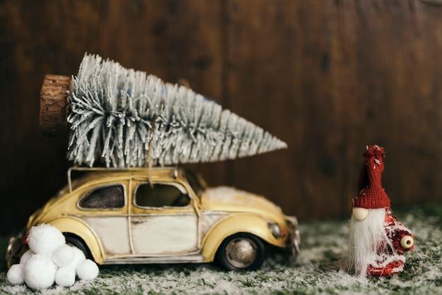 Composizione di natale con un'auto che trasporta un albero di natale Foto Gratuite