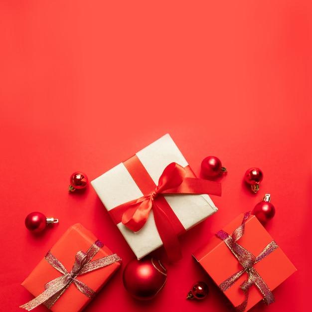Composizione di natale creativo con scatola regalo rosso, nastri, palline rosse grandi e piccole, decorazioni natalizie su rosso. vista piana, vista dall'alto, copyspace Foto Premium