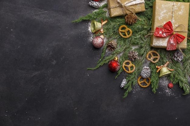 Composizione di natale di rami di conifere, decorazioni e dolci su sfondo scuro. disteso. vista dall'alto natura capodanno concetto. copia spazio. Foto Premium