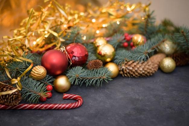 Composizione di natale in oro e palline rosse, caramelle, ghirlande, rami di abete, coni di abete. Foto Premium