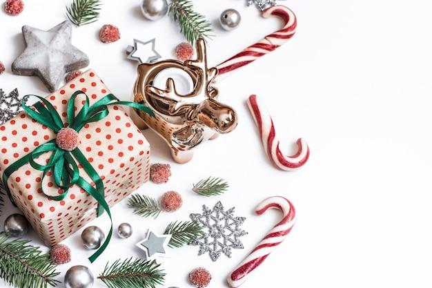Composizione di natale. regali, rami di abete, decorazioni rosse sul muro bianco. inverno, concetto di capodanno. piatto, isometrico, spazio per il testo Foto Gratuite