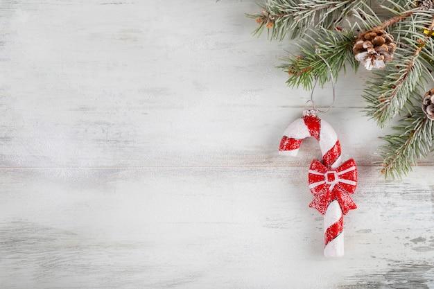 Composizione di natale su un legno coperto di neve bianca. decorazione di festa di capodanno con canna di caramella di natale. copyspace Foto Premium