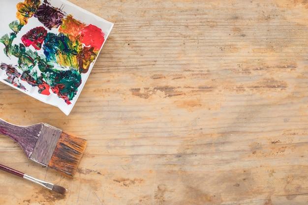 Composizione di pennelli sporchi e carta dipinta Foto Gratuite